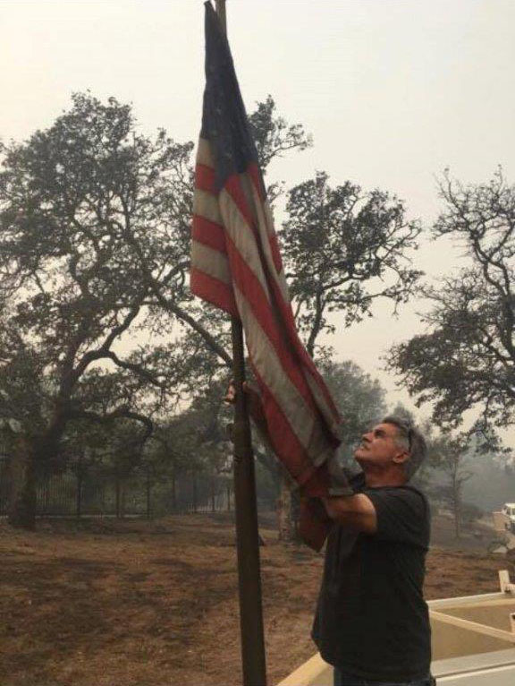 "<div class=""meta image-caption""><div class=""origin-logo origin-image none""><span>none</span></div><span class=""caption-text"">A man raises the American flag at his home that was burned down during the wildfires. (Danielle Funez)</span></div>"
