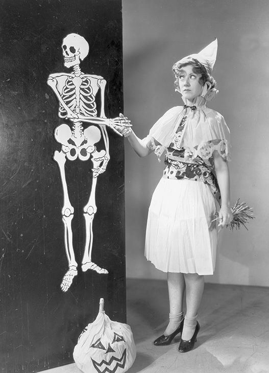 "<div class=""meta image-caption""><div class=""origin-logo origin-image none""><span>none</span></div><span class=""caption-text"">Circa 1935: A costumed woman shakes hands with a life-sized Halloween skeleton decoration hanging on a wall. A paper jack-o'-lantern sits on the floor.  (Hulton Archive/Getty)</span></div>"