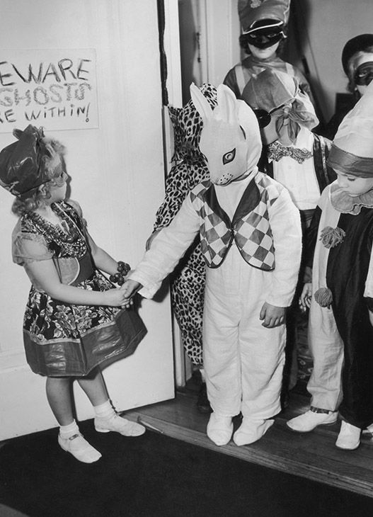 "<div class=""meta image-caption""><div class=""origin-logo origin-image none""><span>none</span></div><span class=""caption-text"">Children in costumes arriving at a Halloween party, USA, circa 1955. A sign on the door warns ""Beware Ghosts are within!"" (Joe Clark/Hulton Archive/Getty)</span></div>"