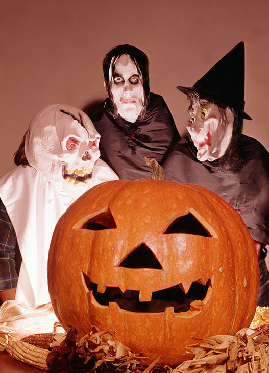 "<div class=""meta image-caption""><div class=""origin-logo origin-image none""><span>none</span></div><span class=""caption-text"">Portrait of three people in Halloween costumes as they pose behind a carved pumpkin, 1965. (Camerique/Getty )</span></div>"