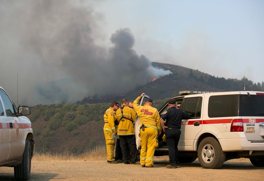 <div class='meta'><div class='origin-logo' data-origin='none'></div><span class='caption-text' data-credit='Rich Pedroncelli/AP Photo'>Firefighters huddle confer as flames from a massive wildfire burn along a mountain top near Oakville, Calif, Friday, Oct. 13, 2017.</span></div>
