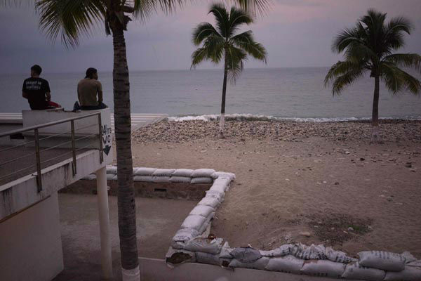 <div class='meta'><div class='origin-logo' data-origin='none'></div><span class='caption-text' data-credit='AP Photo/ Cesar Rodriguez'>Two men sit out by the beach as hurricane Patricia nears in the Pacific resort city of Puerto Vallarta, Mexico, Thursday, Oct. 22, 2015.</span></div>