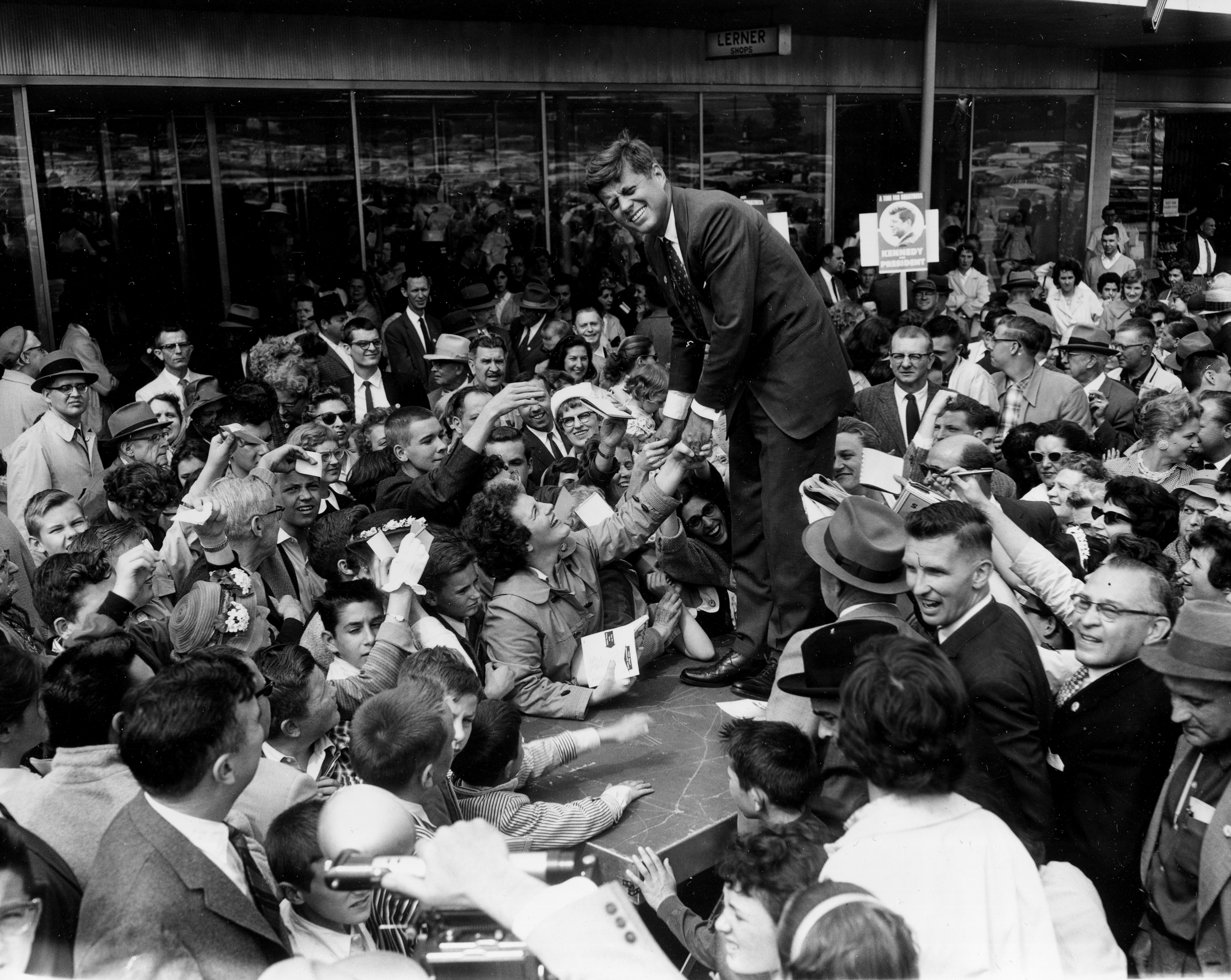 <div class='meta'><div class='origin-logo' data-origin='none'></div><span class='caption-text' data-credit='AP'>U.S. Senator John F. Kennedy, D-Mass., stands on a platform as he shakes hands with a crowd of people that greeted him at Westview shopping center in Baltimore, Md., May 13, 1960.</span></div>