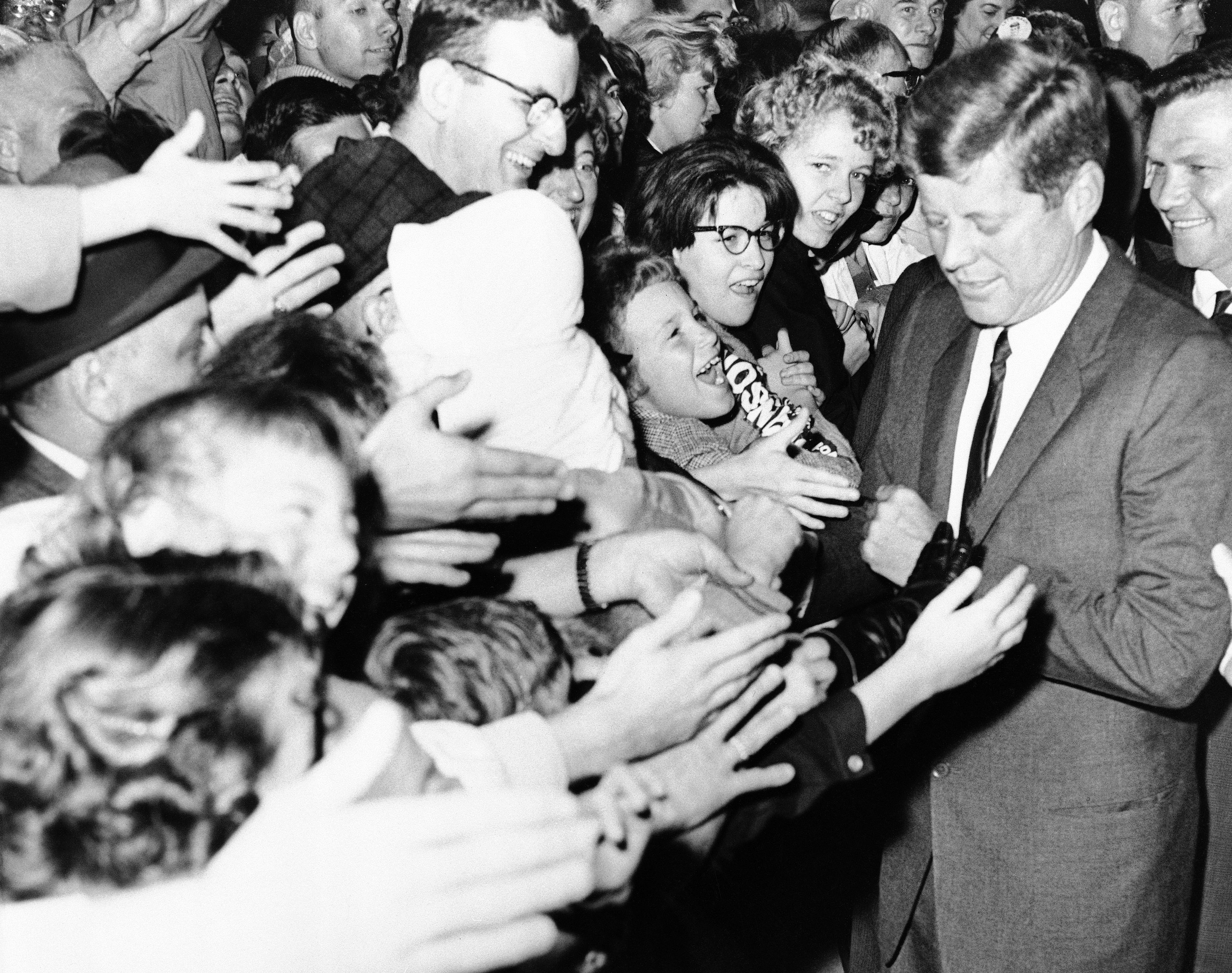 <div class='meta'><div class='origin-logo' data-origin='none'></div><span class='caption-text' data-credit='AP'>President John Kennedy receives an enthusiastic reception after his arrival at Detroit's Metropolitan airport Oct. 5, 1962.</span></div>