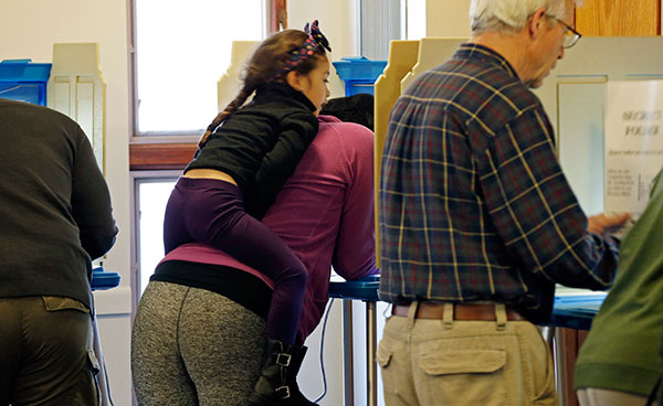 <div class='meta'><div class='origin-logo' data-origin='none'></div><span class='caption-text' data-credit='Jim Mone/AP Photo'>A young girl looks over her mother as she votes Tuesday, Nov. 8, 2016, at a precinct in a Bloomington, Minn. church.</span></div>