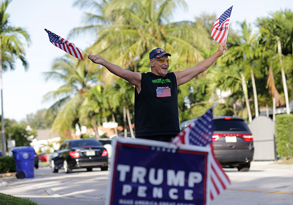 <div class='meta'><div class='origin-logo' data-origin='none'></div><span class='caption-text' data-credit='Lynne Sladky/AP Photo'>Peter Knapp, a supporter of Republican candidate Donald Trump, waves American flags as he stands outside his home on Election Day, Tuesday, Nov. 8, 2016, in Miami.</span></div>