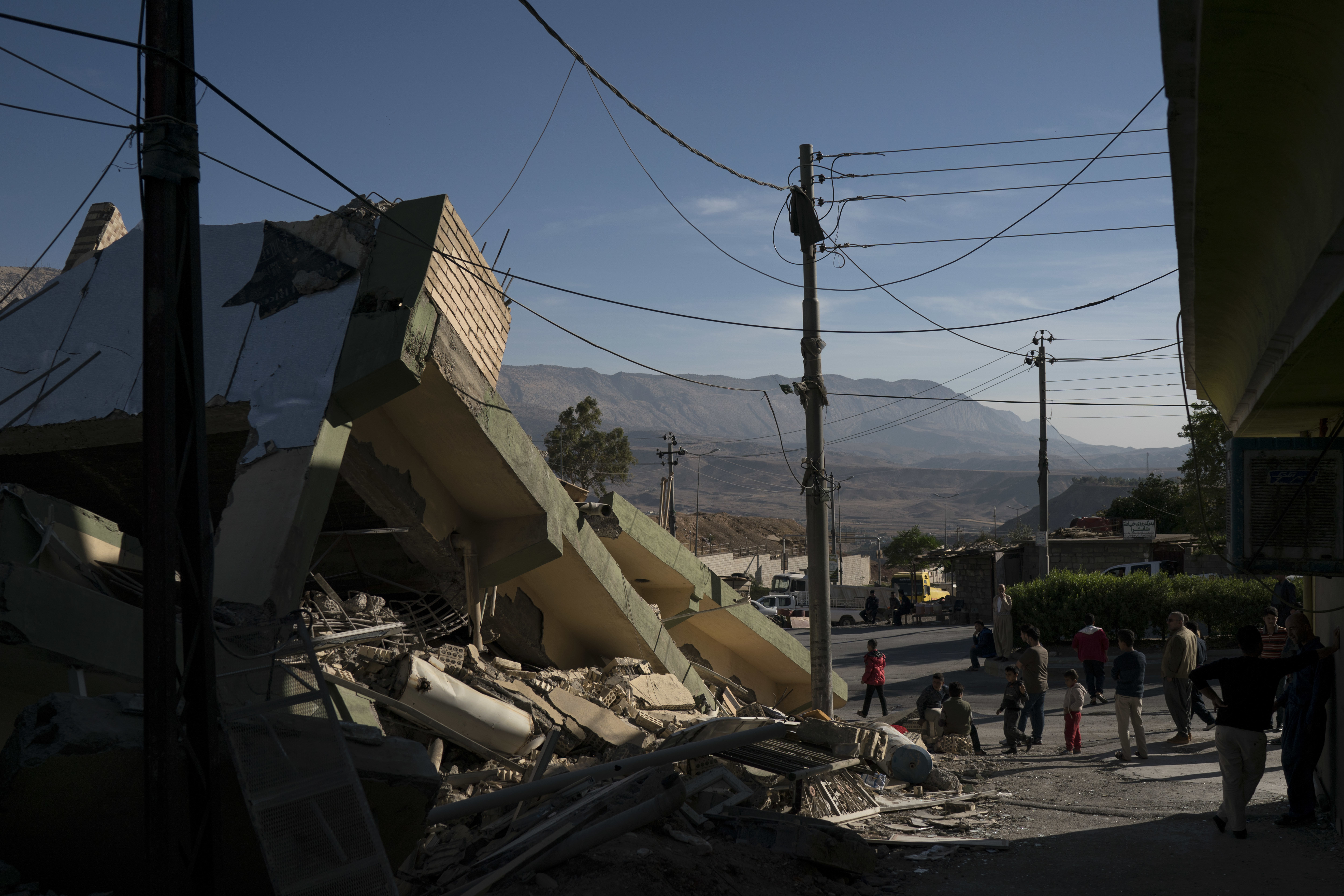 <div class='meta'><div class='origin-logo' data-origin='none'></div><span class='caption-text' data-credit='Felipe Dana/AP Photo'>People walk next to a destroyed house after an earthquake in the city of Darbandikhan, northern Iraq, Monday, Nov. 13, 2017.</span></div>