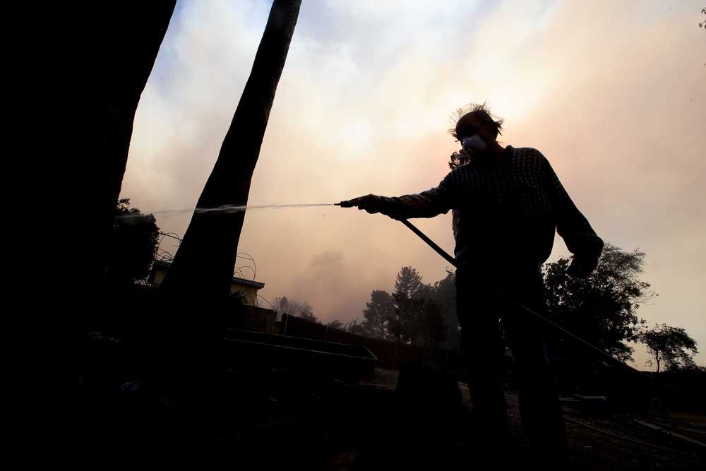 <div class='meta'><div class='origin-logo' data-origin='none'></div><span class='caption-text' data-credit='Chris Carlson/AP Photo'>Homeowner Alan Barnard battles a hot spot from a wildfire in the Lake View Terrace area of Los Angeles on Tuesday, Dec. 5, 2017.</span></div>