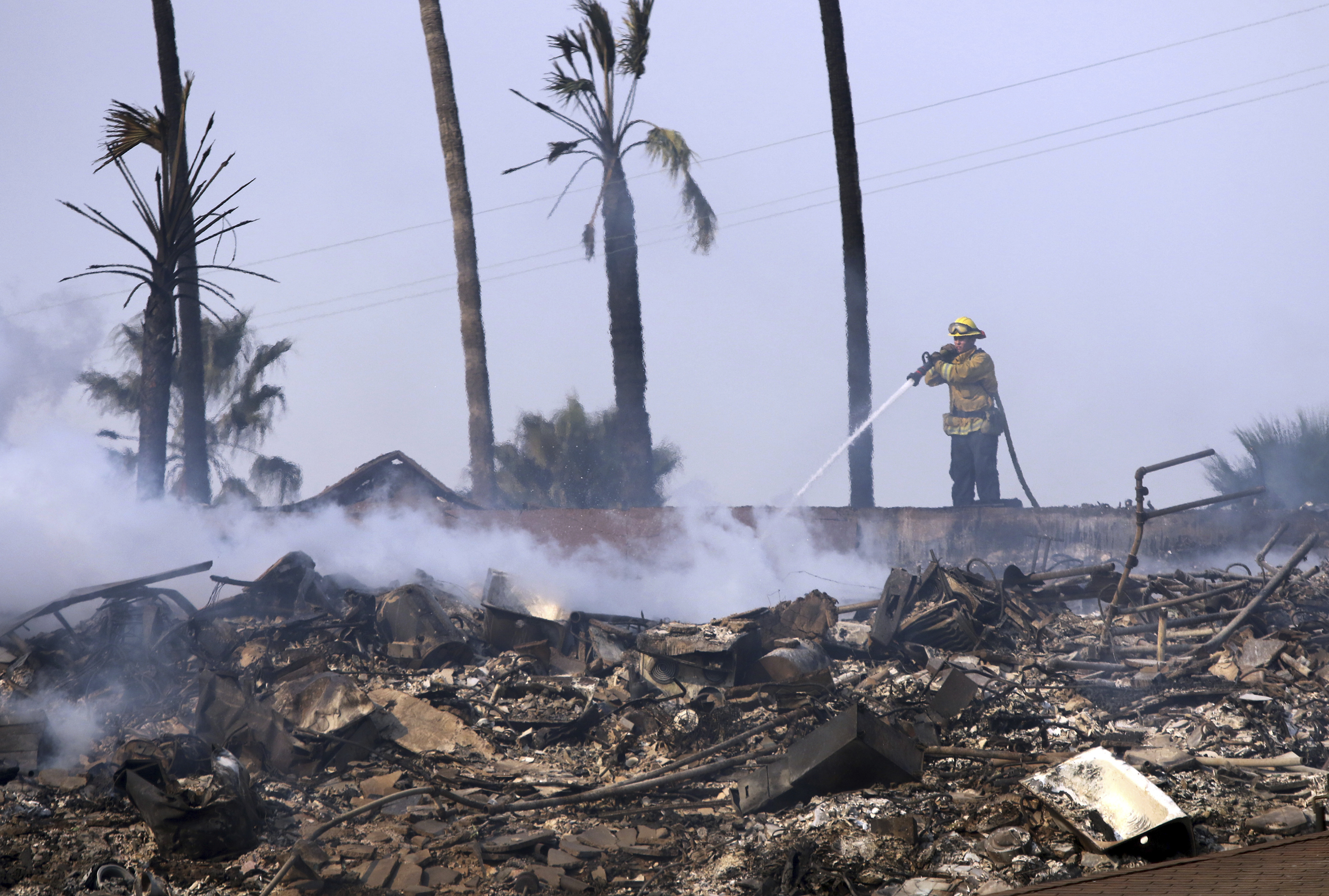 <div class='meta'><div class='origin-logo' data-origin='none'></div><span class='caption-text' data-credit='Daniel Dreifuss via AP'>A firefighter hoses down the remains of a destroyed home after the Thomas fire swept through Ventura, Calif., Tuesday, Dec. 5, 2017.</span></div>