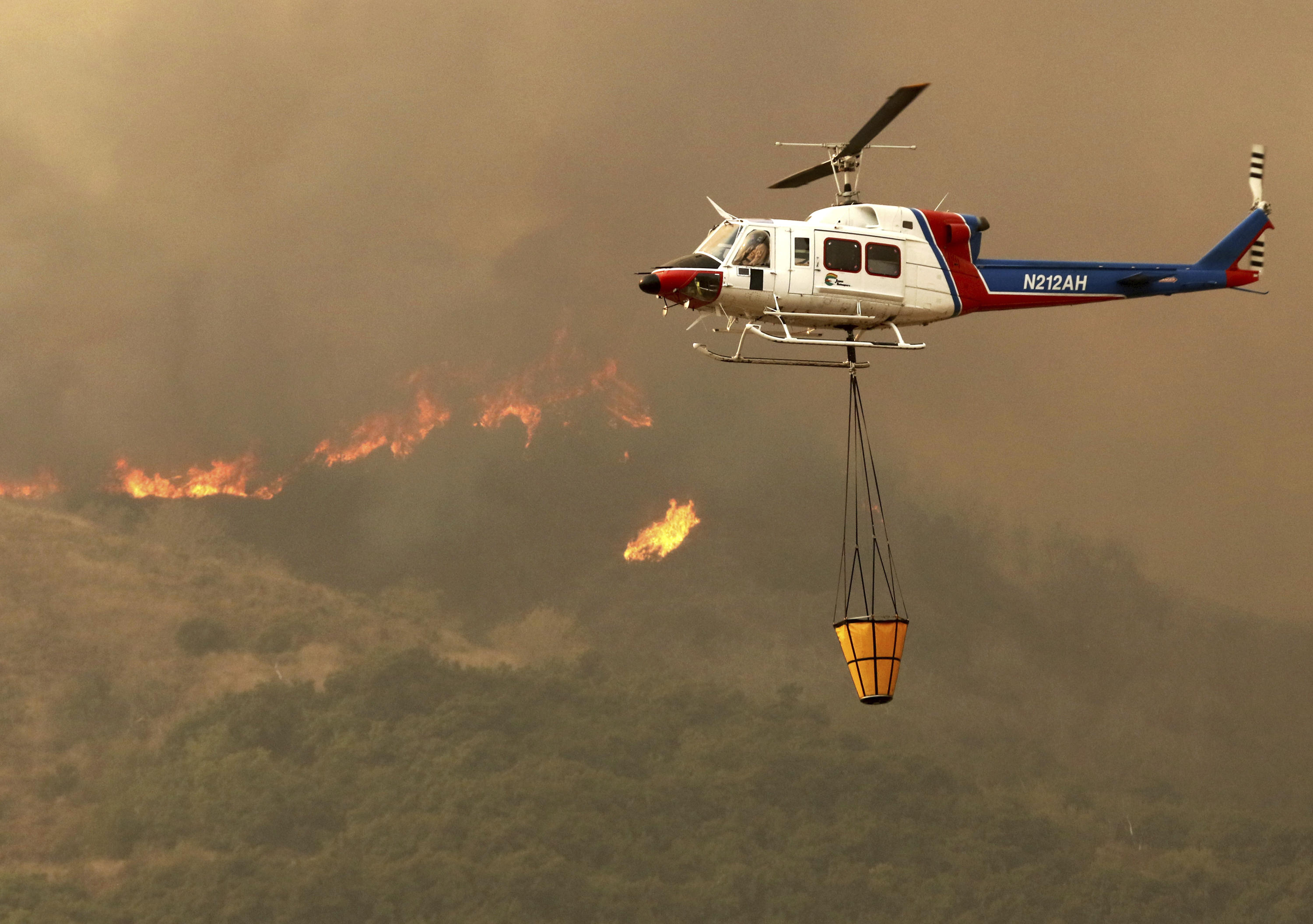 <div class='meta'><div class='origin-logo' data-origin='none'></div><span class='caption-text' data-credit='Daniel Dreifuss via AP'>A helicopter makes a water drop on hot spots after the Thomas fire swept through Ventura, Calif., Tuesday, Dec. 5, 2017.</span></div>