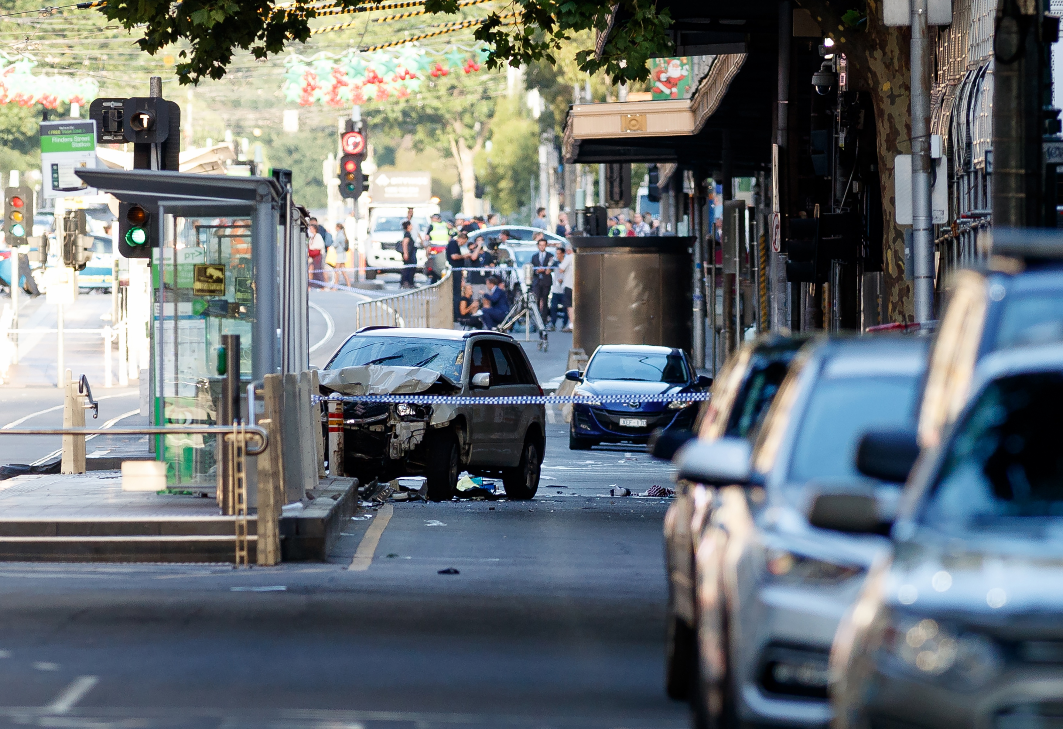 "<div class=""meta image-caption""><div class=""origin-logo origin-image none""><span>none</span></div><span class=""caption-text"">A white SUV (C) sits in the middle of the road as police and emergency personnel work at the scene of where a car ran over pedestrians in Flinders Street in Melbourne. (MARK PETERSON/AFP/Getty Images)</span></div>"