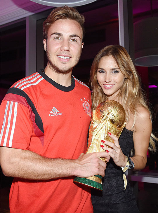 Germany&#39;s Mario Goetze and his girlfriend Ann-Kathrin Broemmel, as they hold the trophy during the German afterparty, after Germany beat Argentina 1-0. <span class=meta>(AP &#47; Markus Gilliar)</span>