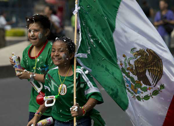 <div class='meta'><div class='origin-logo' data-origin='~ORIGIN~'></div><span class='caption-text' data-credit='AP Photo/ Rebecca Blackwell'>Young fans of the Mexican national soccer team celebrate by the Independence Monument after their team tied with Brazil in their 2014 World Cup soccer match, in Mexico City</span></div>