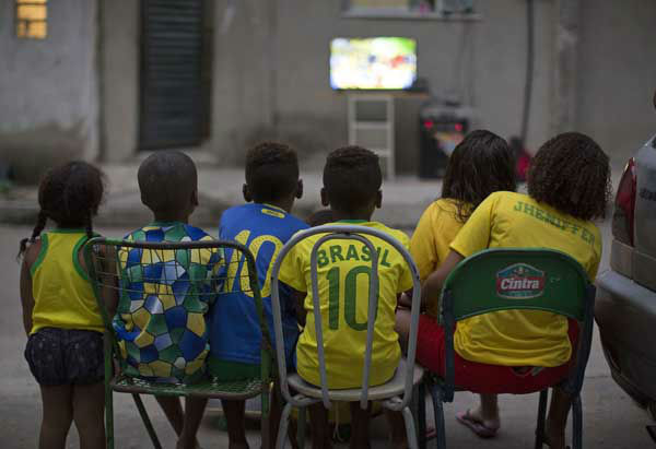 Children watch the World Cup opening match between Brazil and Croatia in an alley at the Mangueira slum, in Rio de Janeiro, Brazil. <span class=meta>AP Photo/ Leo Correa</span>