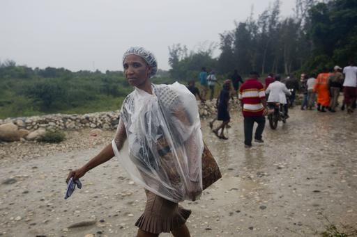 "<div class=""meta image-caption""><div class=""origin-logo origin-image ap""><span>AP</span></div><span class=""caption-text"">A woman protects herself from the rain with a piece of plastic prior the arrival of Hurricane Matthew, in Tabarre, Haiti, Monday, Oct. 3, 2016 (Dieu Nalio Chery)</span></div>"