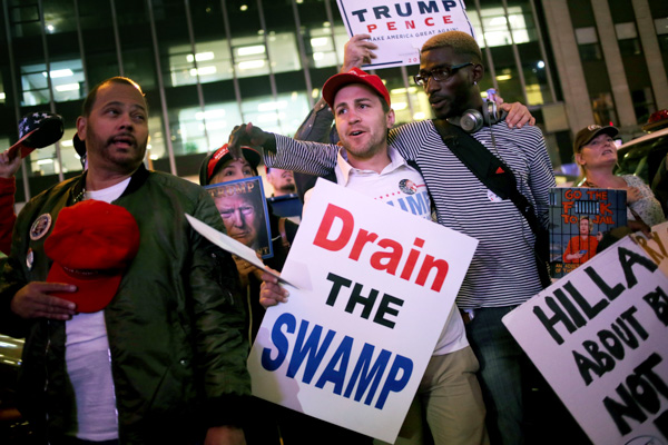<div class='meta'><div class='origin-logo' data-origin='none'></div><span class='caption-text' data-credit='Seth Wenig/AP Photo'>About a dozen supporters of Republican presidential candidate Donald Trump carry signs and sing as they walk through New York on Election Day, Tuesday, Nov. 8, 2016.</span></div>