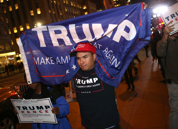 <div class='meta'><div class='origin-logo' data-origin='none'></div><span class='caption-text' data-credit='Seth Wenig/AP Photo'>About a dozen supporters of Republican presidential candidate Donald Trump carry signs and flags as they walk through New York, Tuesday, Nov. 8, 2016.</span></div>