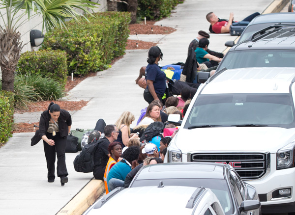 <div class='meta'><div class='origin-logo' data-origin='none'></div><span class='caption-text' data-credit='Wilfredo Lee/AP'>People take cover behind vehicles at Fort Lauderdale-Hollywood International Airport, Friday, Jan. 6, 2017, after a shooter opened fire inside a terminal of the airport.</span></div>