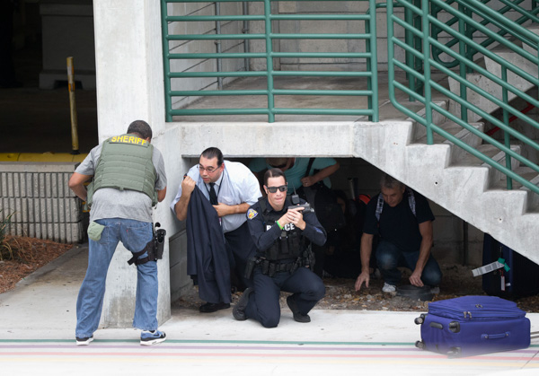 <div class='meta'><div class='origin-logo' data-origin='none'></div><span class='caption-text' data-credit='Wilfredo Lee/AP'>Law enforcement personnel shield civilians outside a garage area at Fort Lauderdale-Hollywood International Airport, after a shooter opened fire inside a terminal.</span></div>