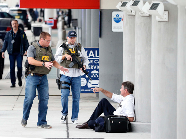 <div class='meta'><div class='origin-logo' data-origin='none'></div><span class='caption-text' data-credit='Wilfredo Lee/AP Photo'>A law enforcement officers talk to a man at Fort Lauderdale-??Hollywood International Airport, Friday, Jan. 6, 2017, in Fort Lauderdale, Fla.</span></div>