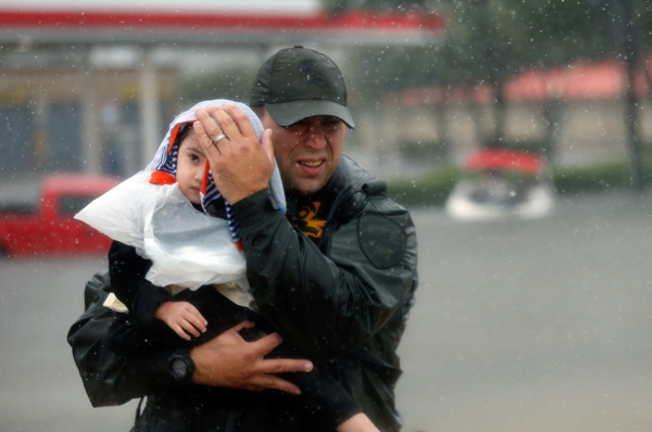 "<div class=""meta image-caption""><div class=""origin-logo origin-image none""><span>none</span></div><span class=""caption-text"">Sgt. Chad Watts, of the Louisiana Department of Wildlife and Fisheries, holds Madelyn Nguyen, 2, after he rescued her and her family by boat from floodwaters. (Gerald Herbert/AP)</span></div>"