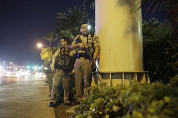 <div class='meta'><div class='origin-logo' data-origin='AP'></div><span class='caption-text' data-credit='AP'>Police officers take cover near the scene of a shooting near the Mandalay Bay resort and casino on the Las Vegas Strip, Sunday, Oct. 1, 2017, in Las Vegas. (AP Photo/John Locher)</span></div>