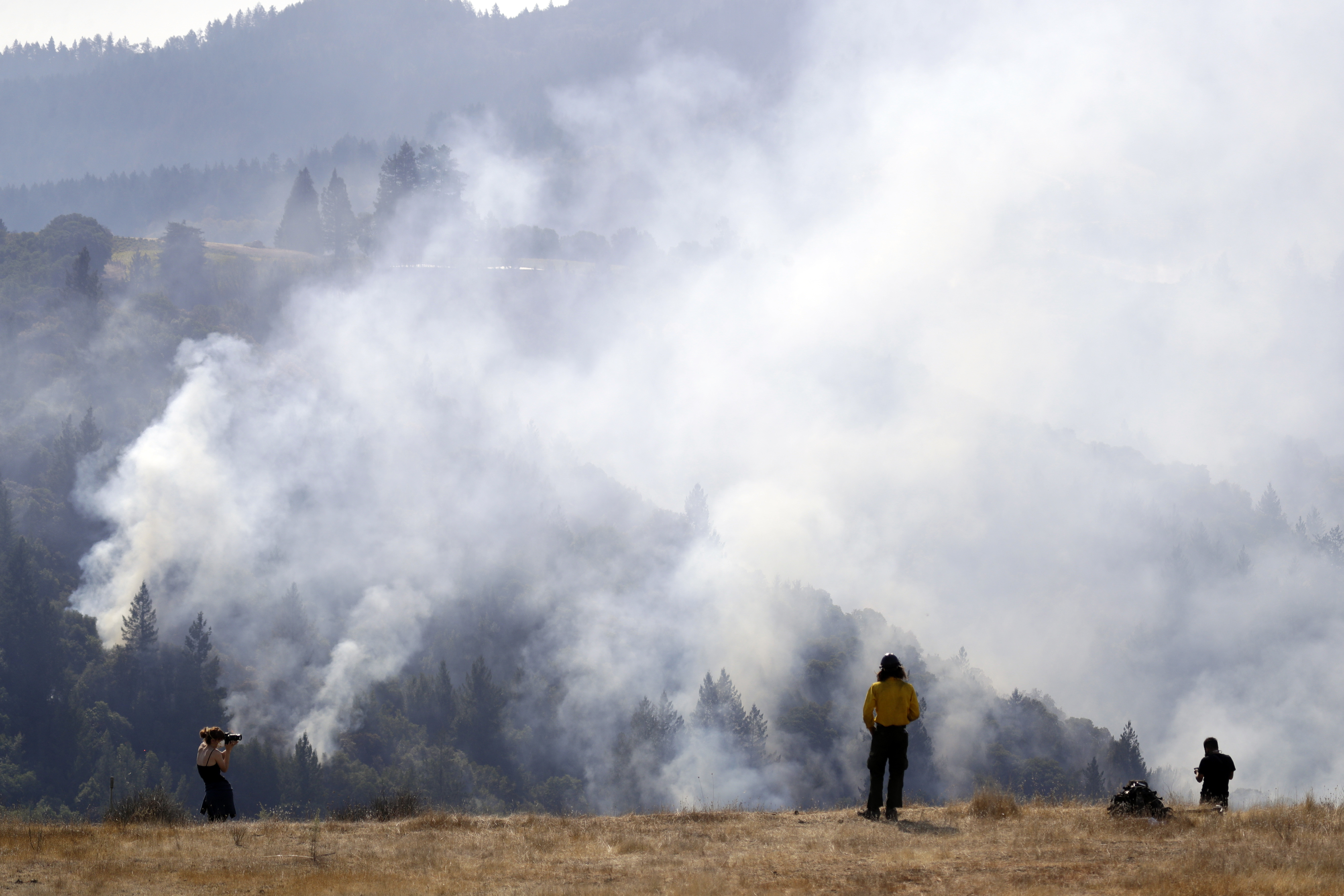<div class='meta'><div class='origin-logo' data-origin='none'></div><span class='caption-text' data-credit='Marcio Jose Sanchez/AP Photo'>A firefighter, center, and two onlookers watch a smoldering wildfire from a hilltop, Sunday, Oct. 15, 2017, in Oakville, Calif.</span></div>