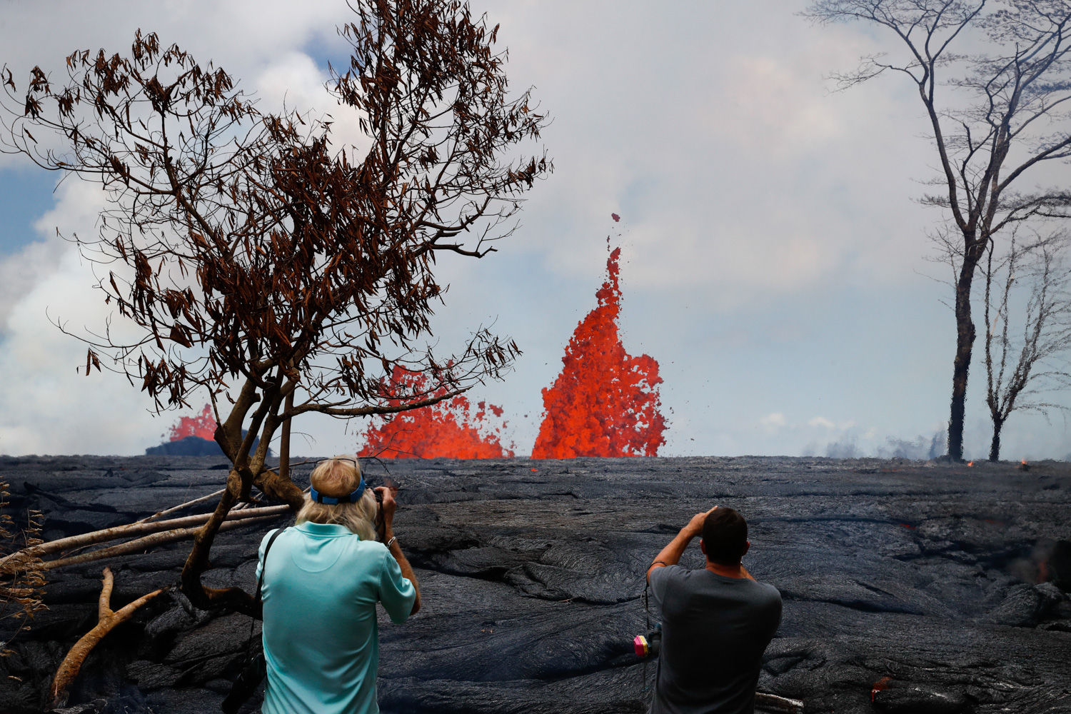<div class='meta'><div class='origin-logo' data-origin='none'></div><span class='caption-text' data-credit='Jae C. Hong/AP Photo'>Heath Dalton, right, and Jim Carpenter take pictures as fissures spew lava in the Leilani Estates subdivision near Pahoa, Hawaii, Tuesday, May 22, 2018.</span></div>