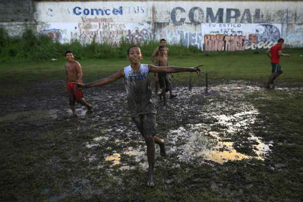 Children play barefoot soccer in a muddy field in Natal, Brazil <span class=meta>AP Photo/ Hassan Ammar</span>
