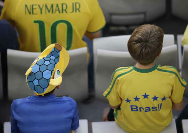 Children in Brazilian colors watch the group F World Cup soccer match between Iran and Nigeria at the Arena da Baixada in Curitiba, Brazil <span class=meta>(AP Photo&#47; Michael Sohn)</span>