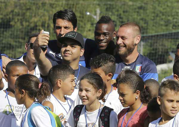 Italy's players, from left, Gianluigi Buffon, Mario Balotelli, and Daniele De Rossi pose for photos with children prior to training in Mangaratiba, Brazil <span class=meta>Photo/Antonio Calanni</span>