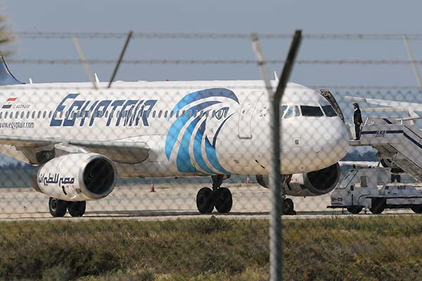 <div class='meta'><div class='origin-logo' data-origin='none'></div><span class='caption-text' data-credit='Petros Karadjias/AP Photo'>A crew member of the hijacked aircraft of EgyptAir is seen on the passenger steps after landing at Larnaca airport Tuesday, March 29, 2016.</span></div>