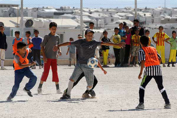 Syrian refugee children play soccer as others watch at the Zaatari refugee camp in Mafraq near the Syrian border in Jordan <span class=meta>AP Photo/ Raad Adayleh</span>