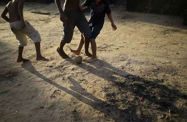 Children play soccer barefoot in front their homes in Tibau do Sul, near Natal, Brazil <span class=meta>AP Photo/ Hassan Ammar</span>