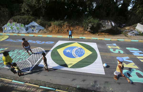 Children play soccer on a street decorated with World Cup related murals in Mangaratiba, Brazil <span class=meta>(AP Photo&#47; Antonio Calanni)</span>