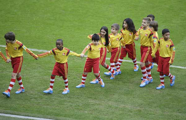 Children hold hands as they leave the pitch after the game opening ceremony they took part in at the beginning of the group H World Cup match between South Korea and Algeria <span class=meta>(AP Photo&#47; Michael Sohn)</span>