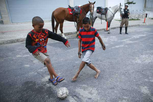 Children play soccer next to mounted police outside the Independencia Stadium <span class=meta>Photo/Victor R. Caivano</span>