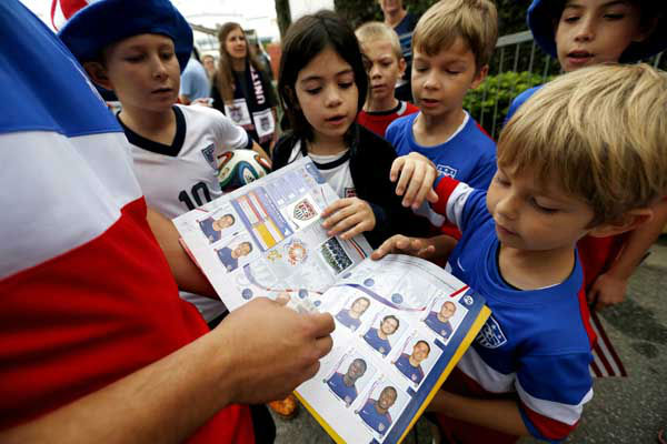 Flavio Aquino, of San Diego, holds up a sticker book with portraits of the U.S. men's soccer team players as children gather around outside the Sao Paulo FC training center <span class=meta>AP Photo/ Julio Cortez</span>