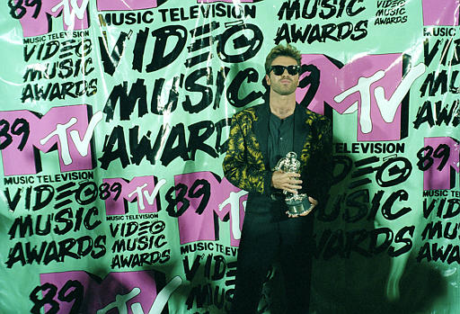 "<div class=""meta image-caption""><div class=""origin-logo origin-image ap""><span>AP</span></div><span class=""caption-text"">Pop singer George Michael displays his trophy after winning the 1989 Video ""Vanguard Award"" for his ""Father Figure"" video during the MTV Music Awards Wednesday, Sept. 6, 1989. (AP Photo/Alan Greth)</span></div>"
