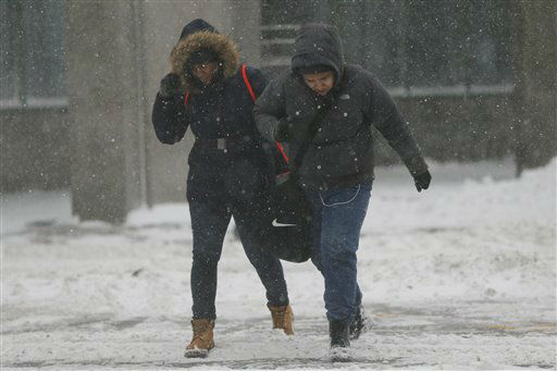 <div class='meta'><div class='origin-logo' data-origin='none'></div><span class='caption-text' data-credit='AP Photo/ Julio Cortez'>People walk on a snow-covered intersection during a snowstorm, Saturday, Jan. 23, 2016, in Jersey City, N.J.</span></div>