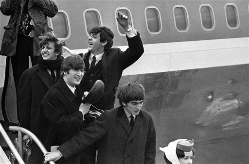 The Beatles make a windswept arrival on Feb. 7, 1964, as they step down from the plane that brought them from London, at Kennedy airport. <span class=meta>AP Photo</span>