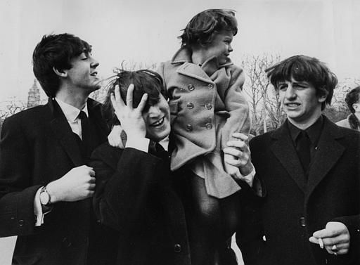 John Lennon, center, holds his forehead as 5-year-old Debbie Fyall, of London, England, sits on his shoulders, in Central Park, February 8, 1964. <span class=meta>AP Photo</span>