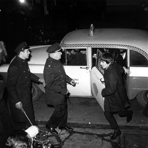 Police security is on hand as guitarist George Harrison leads the way from a taxi-cab to Carnegie Hall's stagedoor on W. 56th St. on Feb. 12, 1964. <span class=meta>AP Photo</span>