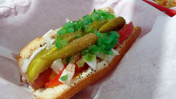 "<div class=""meta image-caption""><div class=""origin-logo origin-image ""><span></span></div><span class=""caption-text"">Chicago-Style dogs feature yellow mustard, white, chopped onions, sliced fresh tomatoes, a dill pickle, piccalilli, sport peppers, and a poppy seed bun. (Bookgrl / Flickr)</span></div>"