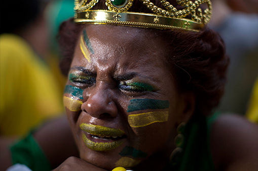 A woman tries to hold back tears after Brazil's loss to Germany. <span class=meta>AP/Dario Lopez-Mills</span>