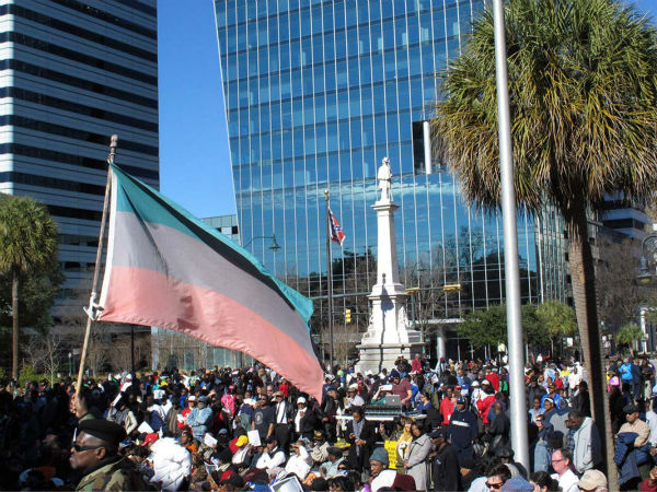 """<div class=""""meta image-caption""""><div class=""""origin-logo origin-image """"><span></span></div><span class=""""caption-text"""">A crowd listens to speakers at the annual King Day at the Dome rally as the Confederate flag flies on the grounds of the South Carolina Statehouse on Monday, Jan. 19, 2015.  (AP Photo/Jeffrey Collins)</span></div>"""