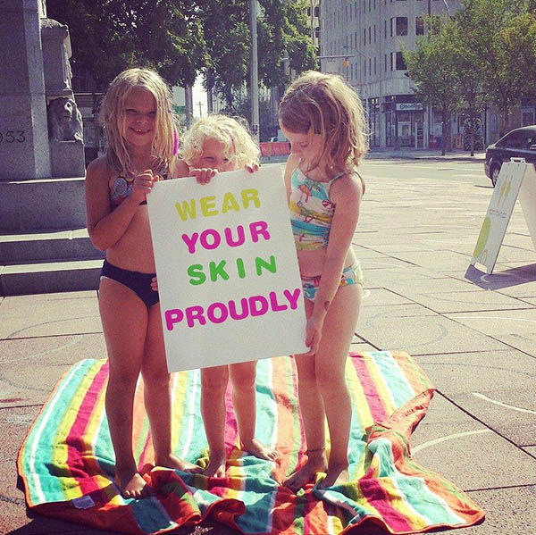 "<div class=""meta ""><span class=""caption-text "">Three children at the event holding a sign that says ""Wear your skin proudly."" (Kristin Heimbecker / Facebook)</span></div>"