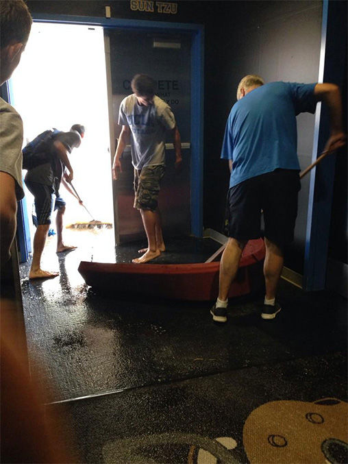 Students try to save the locker room with brooms and barricades. <span class=meta>(miss_alexpham &#47; Twitter)</span>