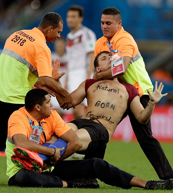 A spectator who ran on to the pitch during the World Cup final soccer match between Germany and Argentina is subdued by security personnel at the Maracana Stadium. <span class=meta>(Natacha Pisarenko)</span>