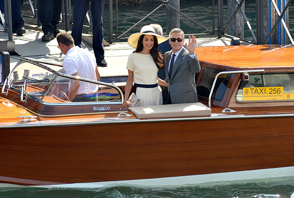 """<div class=""""meta image-caption""""><div class=""""origin-logo origin-image """"><span></span></div><span class=""""caption-text"""">George Clooney, flanked by his wife Amal Alamuddin, waves from a water-taxi after leaving Venice's city hall following their civil marriage ceremony on Monday, Sept. 29, 2014. (AP Photo/Luigi Costantini)</span></div>"""